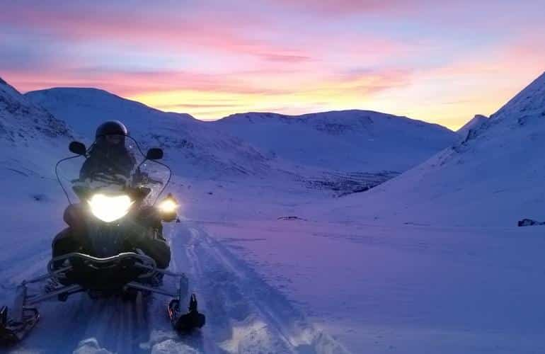 Snowmobiling in the evening during a full-day excursion in Tromsø