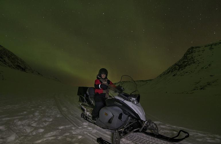 Snowmobiling in Tromsø with the Northern Lights in the background