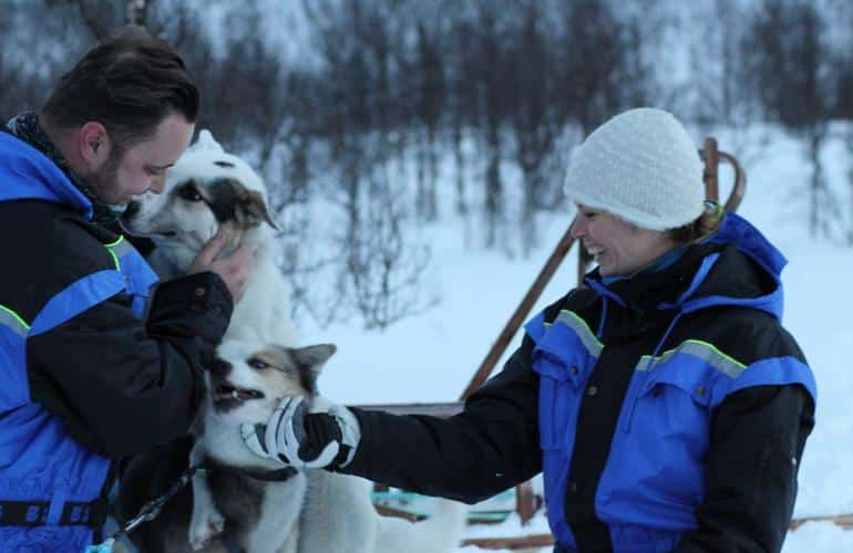 Dog sled participants playing with the dogs