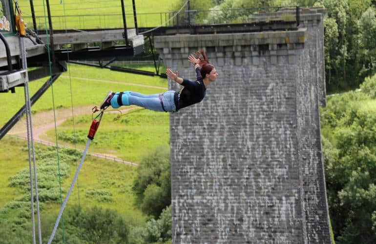 Woman bungee jumping from the Souleuvre Viaduct in Normandy