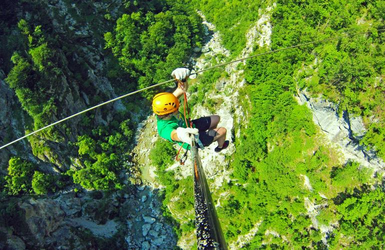 Man zip lining in th emountains of Bovec in Slovenia