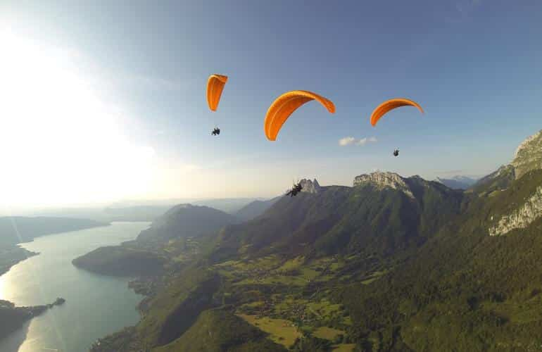 Paraglides flying above the Annecy Lake